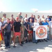 foto účastníků zájezdu do jordánské Petry – Lukáš stojí vpravo vedle  plachty s logem